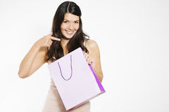 Happy shopper pointing to her shopping bag Royalty Free Stock Images