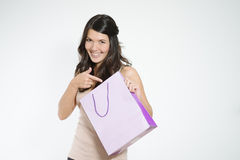 Happy shopper pointing to her shopping bag Stock Image