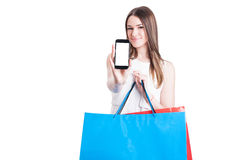 Happy shopper with shopping bags showing a blank smartphone scre Stock Images