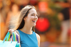 Happy shopper with shopping bags walking. Portrait of a happy shopper with shopping bags walking on the street royalty free stock photos