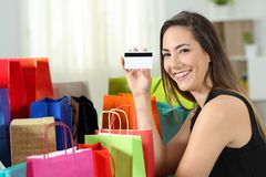 Happy shopper showing a credit card at home royalty free stock photos