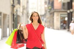 Happy shopper walking holding bags in the street royalty free stock image