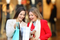 Happy shoppers checking purchases in a shooping bag. Front view of two happy shoppers checking purchases in a shooping bag in a commercial centre stock photography