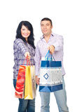 Happy shoppers couple give bags. Happy shoppers couple giving you their shopping bags isolated on white background Stock Photo