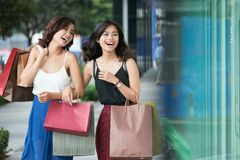 Happy shoppers. Happy laughing young Asian women with many shopping bags Royalty Free Stock Images