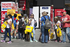 Happy shoppers with yellow packets of M Royalty Free Stock Photo