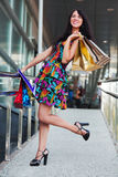Happy fashion woman with shopping bags in the mall Stock Image