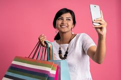 Happy shopping asian woman taking selfie. While holding a lot of shopping bags stock image