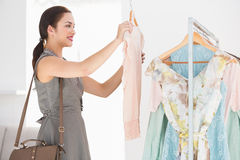 Happy shopping brunette looking at shirt Stock Photo