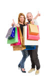 Happy shopping couple showing thumbs up. Standing  isolated on white backrgound Royalty Free Stock Photography