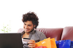 Happy shopping online. A young man  using his credit card to purchase over the internet, happiness and amazement Royalty Free Stock Photography