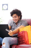 Happy shopping online. A young man  using his credit card to purchase over the internet, happiness and amazement Royalty Free Stock Image
