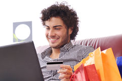 Happy shopping online. A young man  using his credit card to purchase over the internet, happiness and amazement Royalty Free Stock Photos