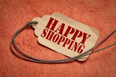 Happy shopping on a price tag with a twine. Happy shopping on a paper price tag with a twine against textured orange bark paper stock photos