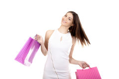 Happy shopping, smiling female with colorful shopping bags. Happy female rejoice at shopping, dancing, with colored paper bags, copy space, isolated on white Royalty Free Stock Photo