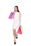 Happy shopping smiling girl carrying colorful shopping bags. Happy female shopping, dancing with colored paper bags, copy space, isolated on white background Royalty Free Stock Photo