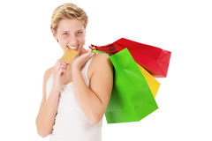 Happy shopping woman bites on her credit card Stock Photos