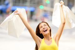 Happy shopping woman in excited winning. And cheering holding shopping bags up in air. Shopper on shopping spree. Young multiracial Asian Caucasian girl in Royalty Free Stock Images