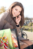 Happy Shopping: Woman with her purchase and phone. Woman checking her purchase outdoor and talking on the mobile phone Royalty Free Stock Photography
