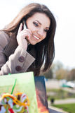 Happy Shopping: Woman with her purchase and phone. Woman checking her purchase outdoor and talking on the mobile phone Stock Images