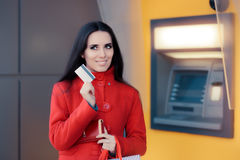 Happy Shopping Woman Holding Credit Card in front of an ATM. Cute shopper girl spending wisely Stock Photo