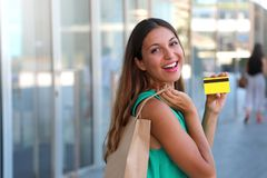 Happy shopping woman showing her credit card. Girl with shopper bag holding her credit card and show it at the camera. Happy shopping woman showing her credit royalty free stock photos
