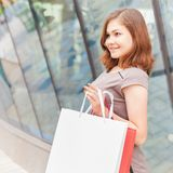 Happy shopping woman with a white bag outdoor Royalty Free Stock Images