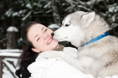 Happy siberian husky owner with dog. Happy positive siberian husky owner facing to dog snout at winter outdoors Royalty Free Stock Image