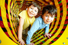 Happy siblings. Looking at camera while having fun inside toy tunnel royalty free stock photo