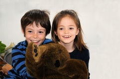 Happy siblings. Siblings are playing  together with a plush toy Royalty Free Stock Photography