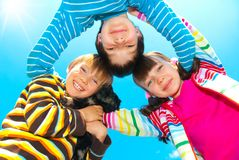 Happy Siblings. A portrait of cute happy siblings and their pet dog, on the backdrop of a blue sky royalty free stock photography