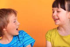 Happy Siblings. A portrait of a cute happy siblings laughing, on orange background stock photo