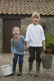 Happy Siblings With Buckets By Stable Royalty Free Stock Images