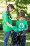 Happy siblings collecting rubbish. On a sunny day stock photo