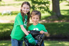 Happy siblings collecting rubbish. On a sunny day Royalty Free Stock Photos