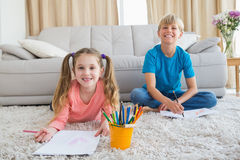 Happy siblings colouring on the rug Royalty Free Stock Photography