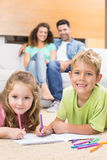 Happy siblings colouring on the rug with parents watching from sofa Royalty Free Stock Photos