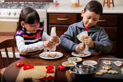 Happy siblings decorating cookies Royalty Free Stock Photos
