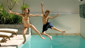 Happy siblings diving into the swimming pool stock video footage