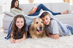 Happy siblings with dog under blanket Stock Images