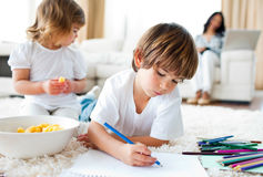 Happy siblings eating chips and drawing. In the living-room royalty free stock image