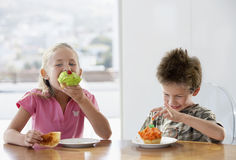 Happy Siblings Eating Cup Cakes At Dining Table Royalty Free Stock Image