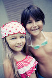 Happy siblings enjoying summer. By poolside stock photography