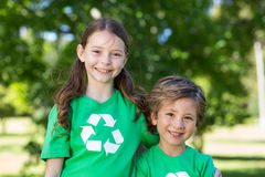 Happy siblings in green smiling at the camera. On a sunny day stock images