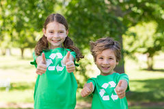 Happy siblings in green with thumbs up Stock Photos