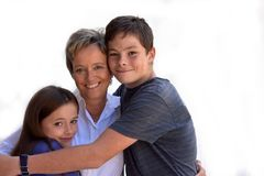 Happy siblings. Brother and sister embracing her mother stock photography
