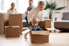 Happy siblings playing riding in box moving into new home stock photos