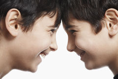 Happy Siblings With Head To Head Against White Background Stock Photos