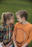 Happy siblings holding badminton racquets and smiling each other. Cute happy siblings holding badminton racquets and smiling each other royalty free stock photos