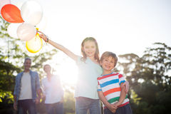 Happy siblings holding balloons at the park Royalty Free Stock Photo